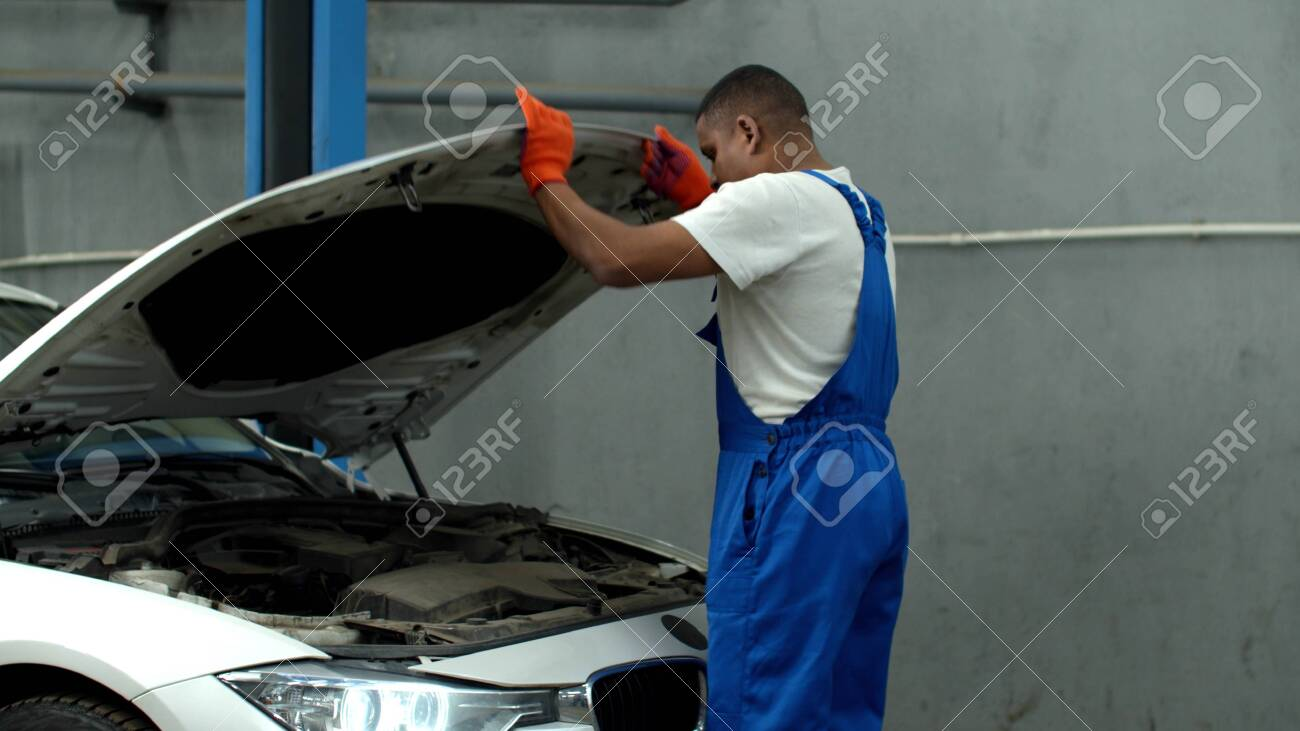 Mechanic opens the hood of a car and looks at the motor - 140903924