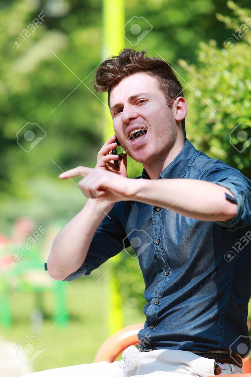 Young red hair man in the park talk on telephone Stock Photo - 14227696