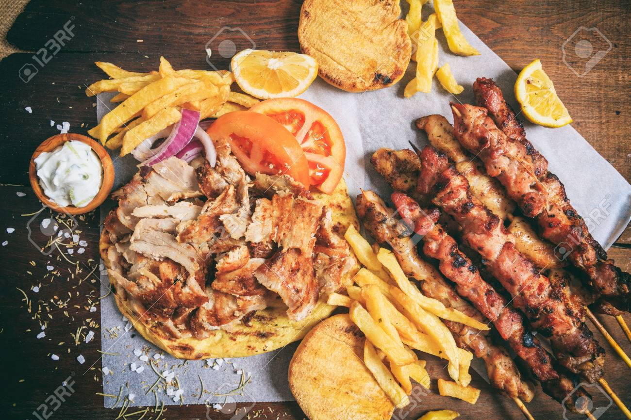 Greek gyros dish and meat skewers on a wooden background - 71298691