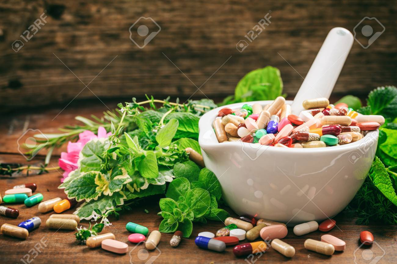 Variety of herbs and pills in a mortar on wooden background. - 75920323