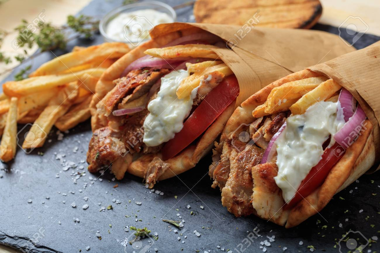 Greek gyros wrapped in pita breads on a black plate - 76406526