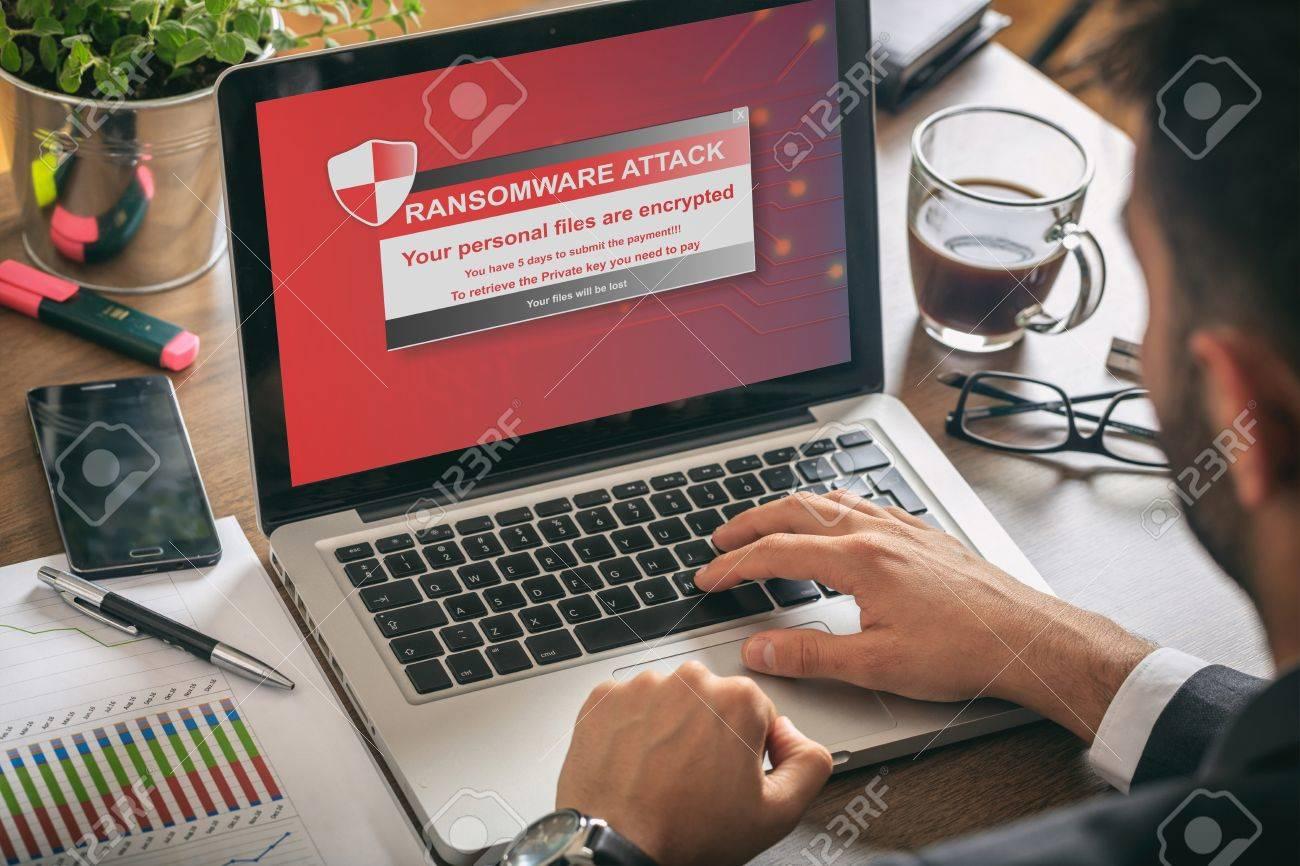 Ransomware alert message on a laptop screen - man at work - 80433638