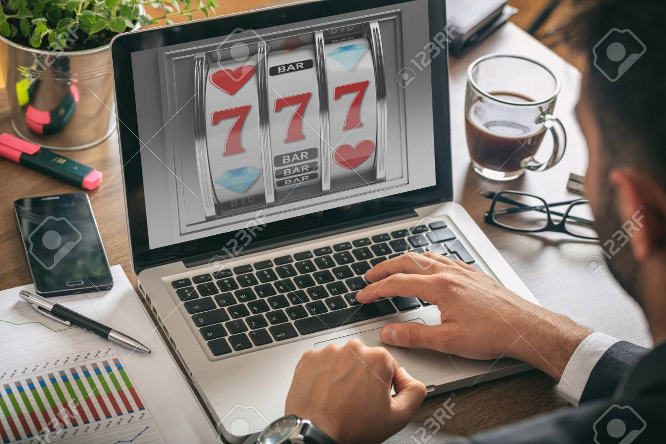 Online gambling concept. Man with a laptop, slot machine on the screen, office background - 87572214