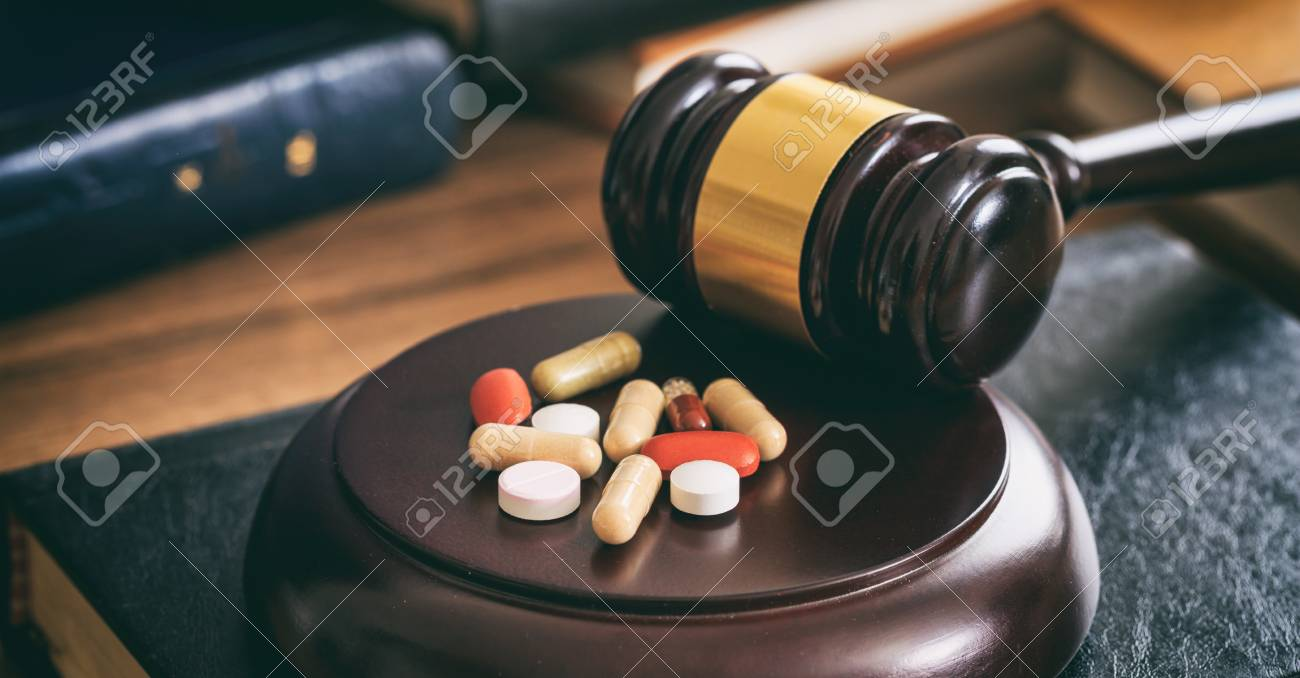 Law gavel and colorful pills on a wooden desk, dark background - 88331525