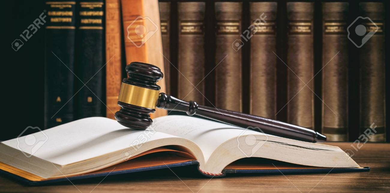 Law gavel on an open book, wooden desk, law books background - 88331529