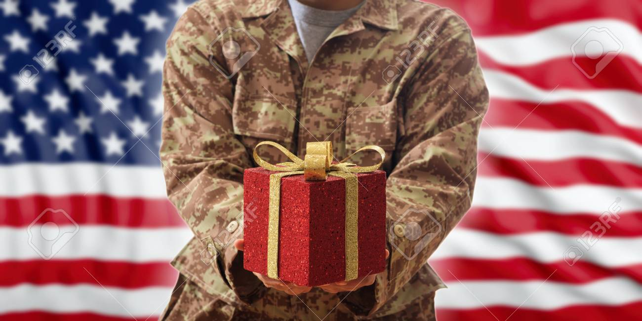 Christmas in the army concept. Christmas ball and gift box on an American soldier uniform - 90013826