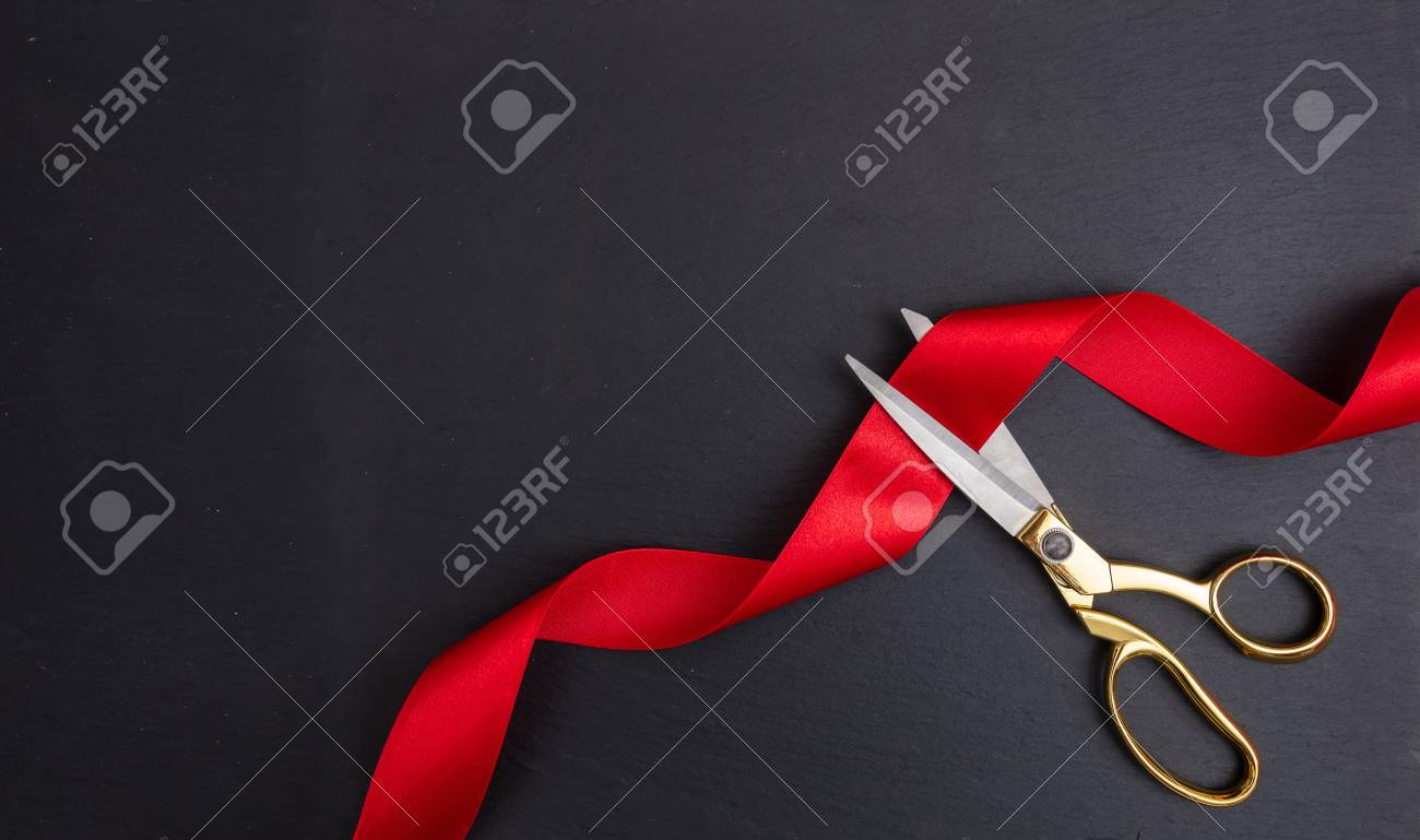 Grand opening. Top view of gold scissors cutting red silk ribbon against black background, copy space - 114522505