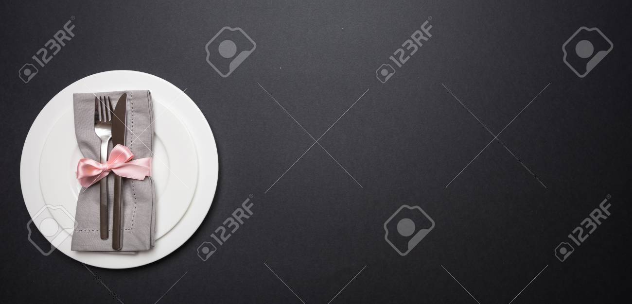 Table place setting with linen napkin, pink ribbon and white plates on black color background, banner, top view, copy space - 117565986