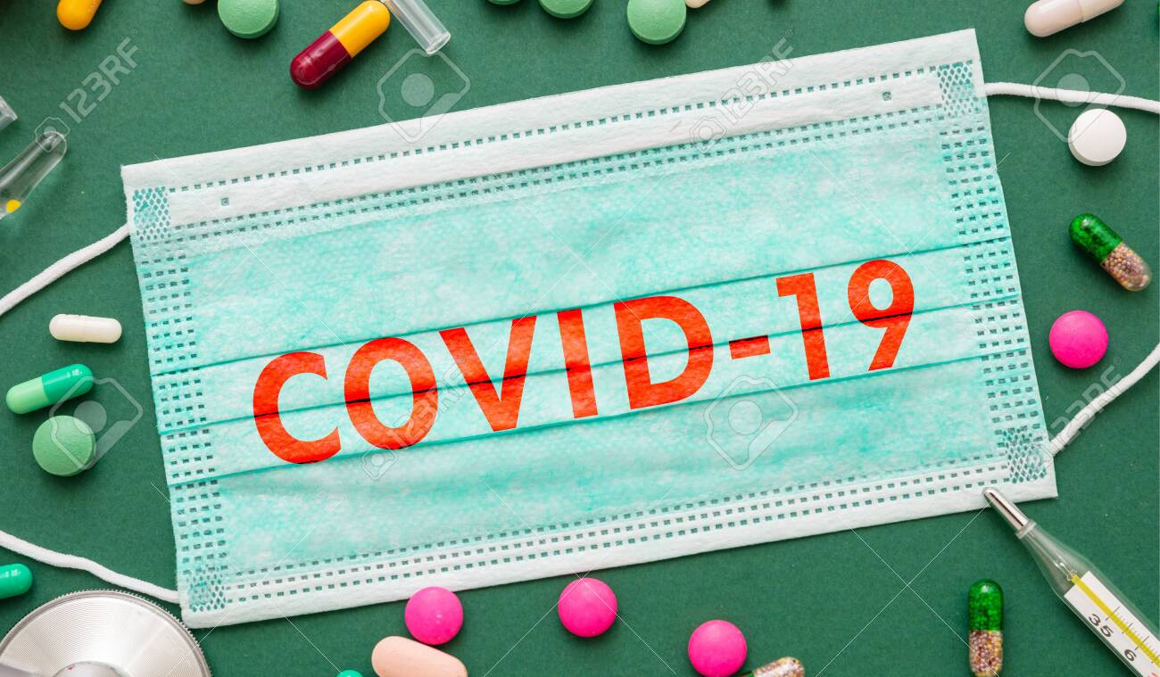 Coronavirus protective measures amd treatment. COVID 19 text on surgical mask, medical supplies and medication on green background, top view - 144630028