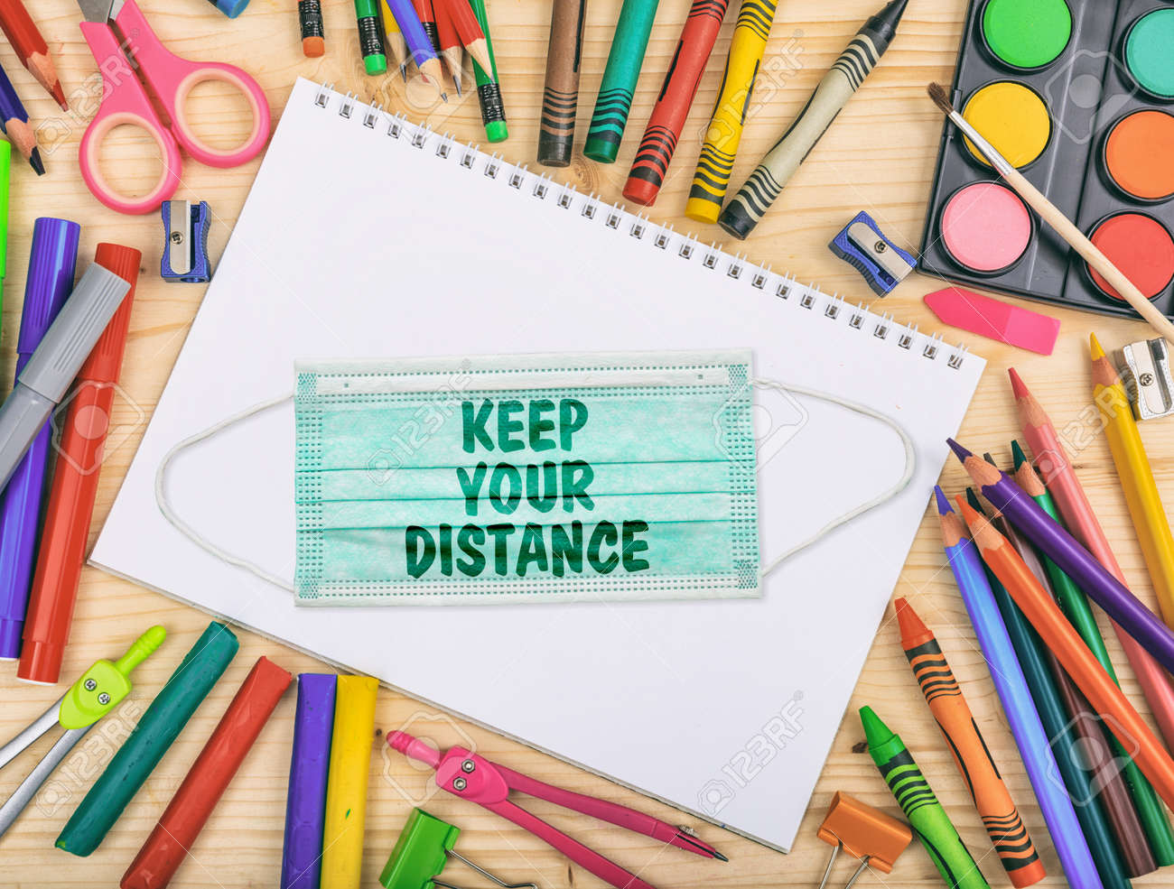 KEEP YOUR DISTANCE text message on a medical protective mask, school supplies flat lay, Back to school, coronavirus days - 155163227