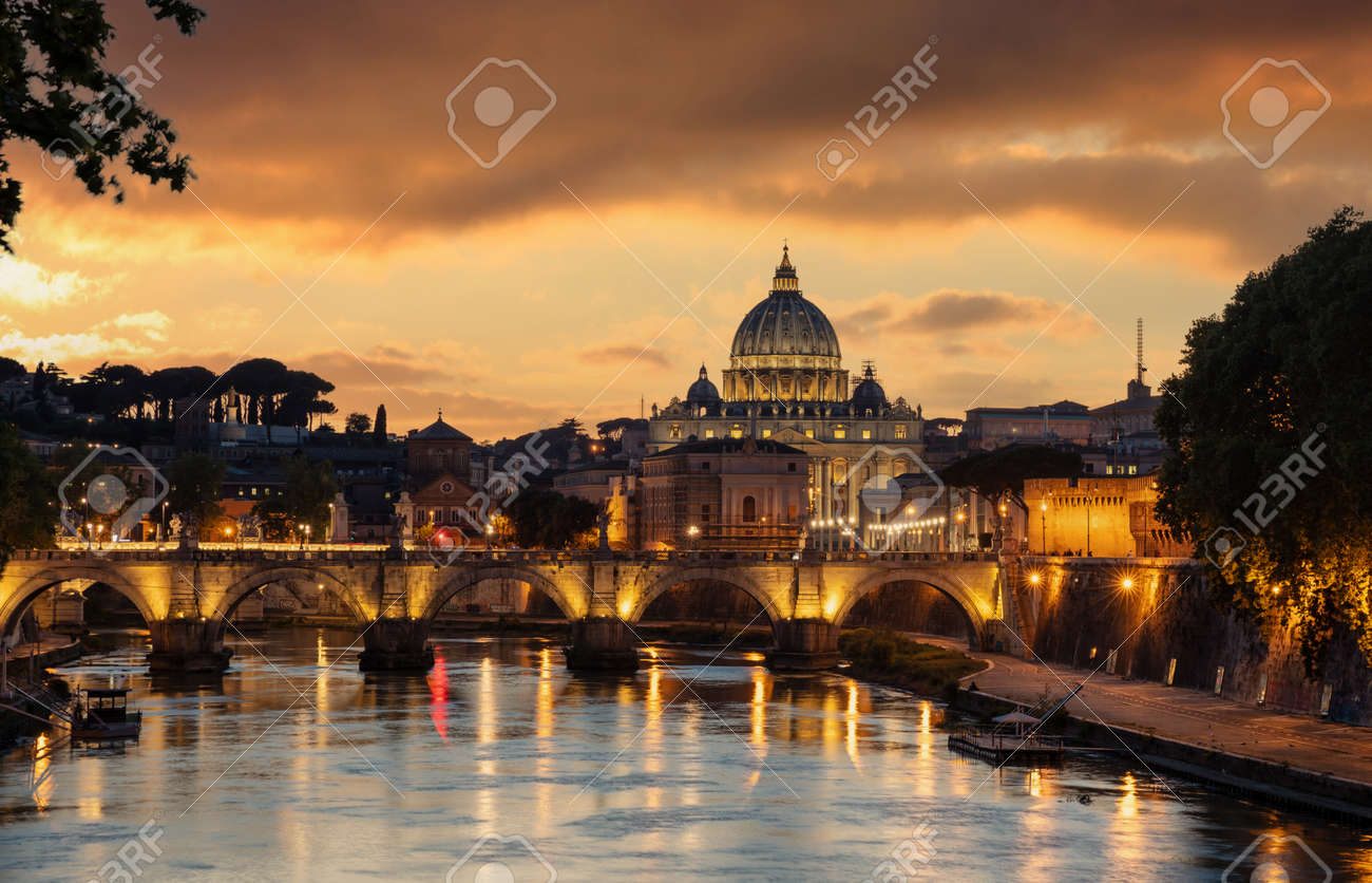 Rome Italy. Saint Peter Basilica in the Vatican over illuminated Sant Angelo bridge and Tiber river night view, orange color sky after sunset - 167214444