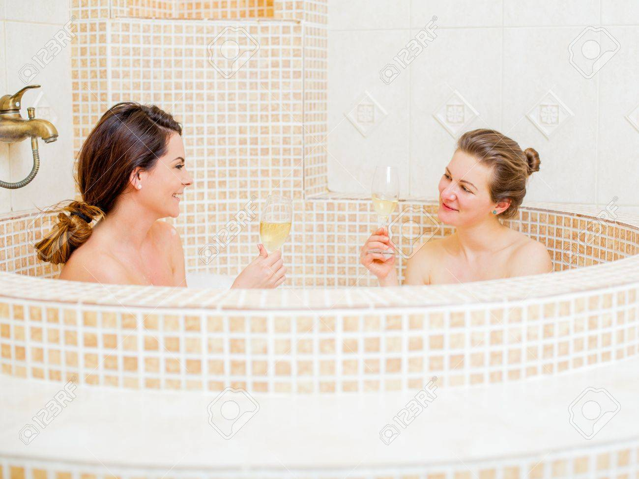 Gorgeous gay couple celebrating in the foam bath at home. Stock Photo -  41558971