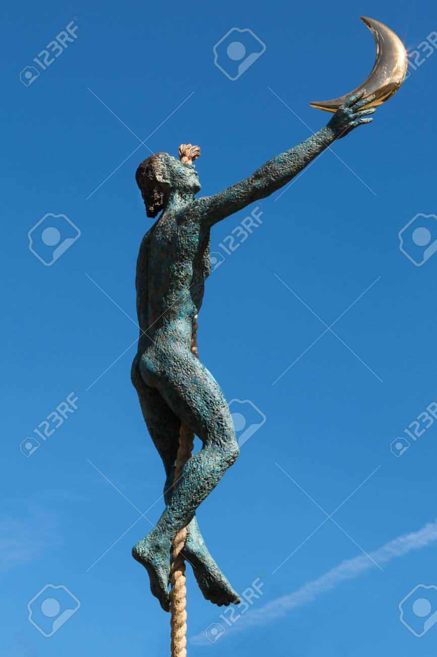 Little Bronze Statue Man Over A Rope Catching The Moon Stock Photo