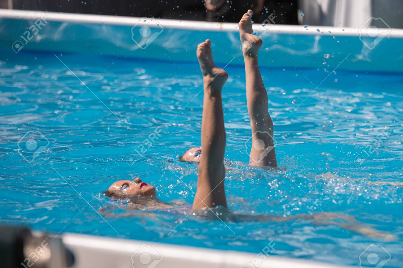 Performing Artistic Duet in Swimming Pool: Synchronized Swimming..