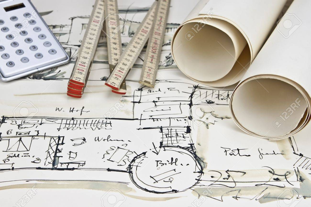 the blueprint of a house with two paper rolls a calculator and