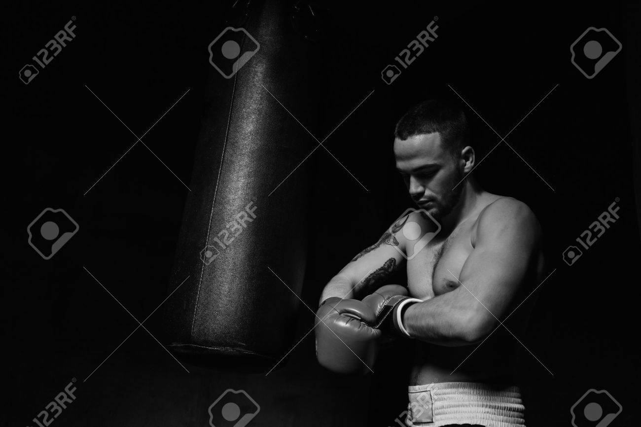 Boxer man putting on boxing gloves in dark room black and white shot stock photo