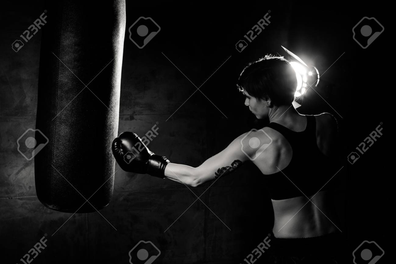 dramatic studio lighting. Athlete Boxer Woman Punching A Bag With Dramatic Lighting In Dark Studio. Black Studio L