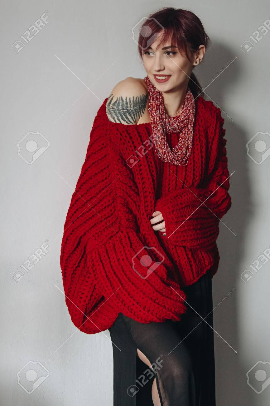 e93fdcf5c5 Portrait of young woman in stylish red oversized sweater and black skirt  with tattoo on shoulder