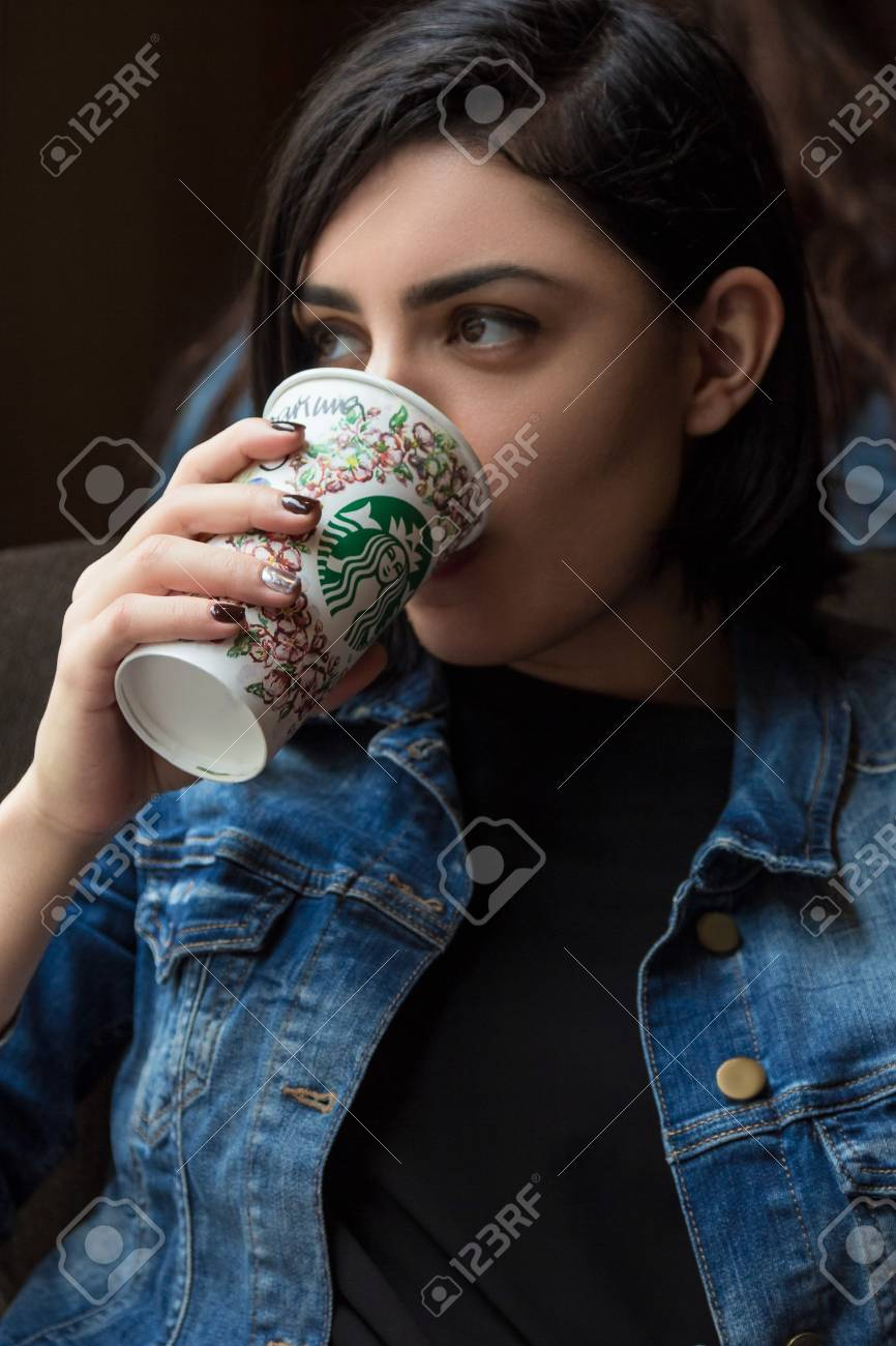 BARCELONA, SPAIN - APRIL 22, 2016: Beautiful young woman drinking coffee at Starbucks cafe in Barcelona - 76121260