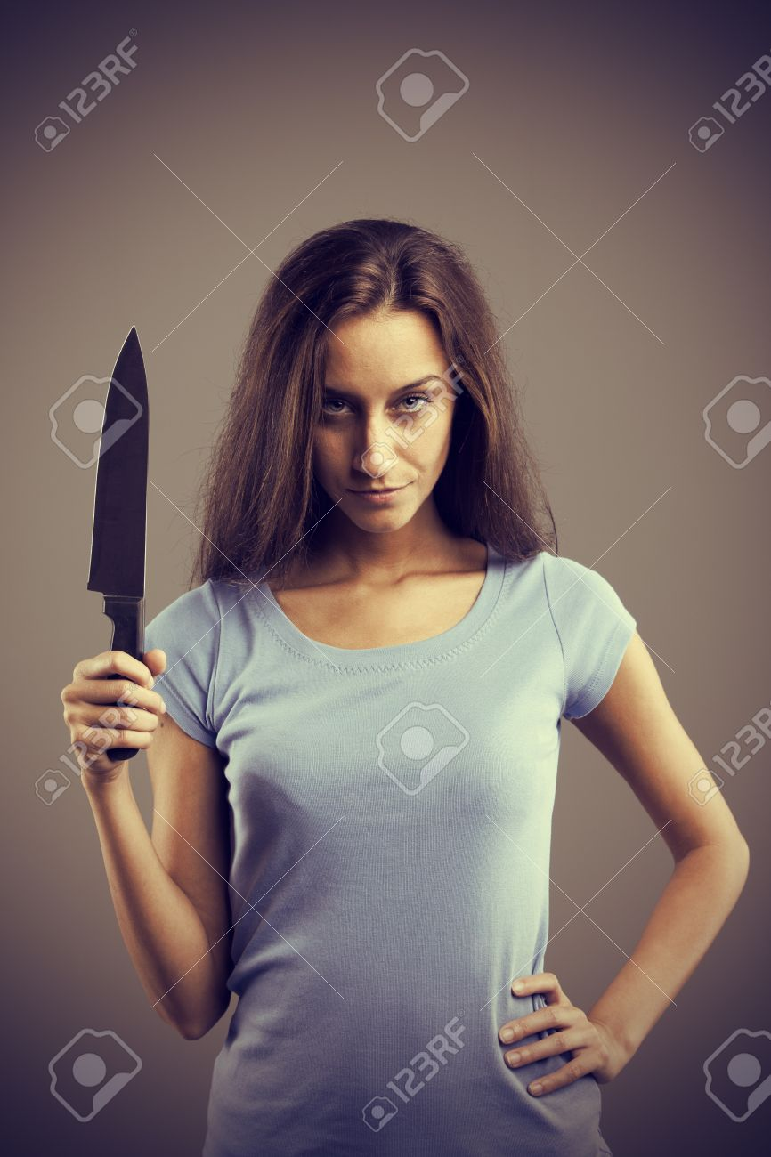 Unsettling dark young woman holding a dengerous knife in his