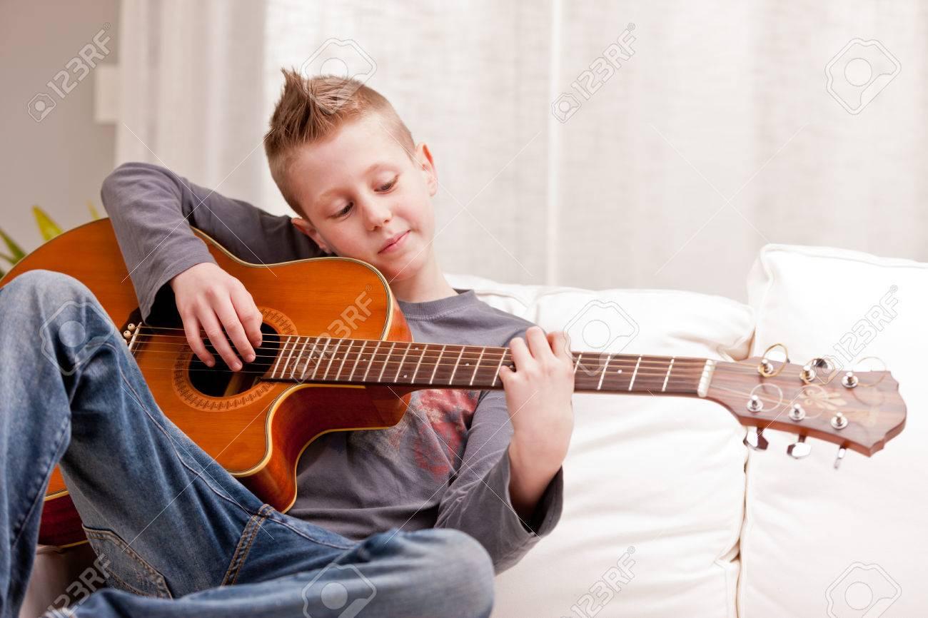 Kleiner Junge Spielt Gitarre Auf Einem Sofa In Seinem Wohnzimmer Lizenzfreie Bilder