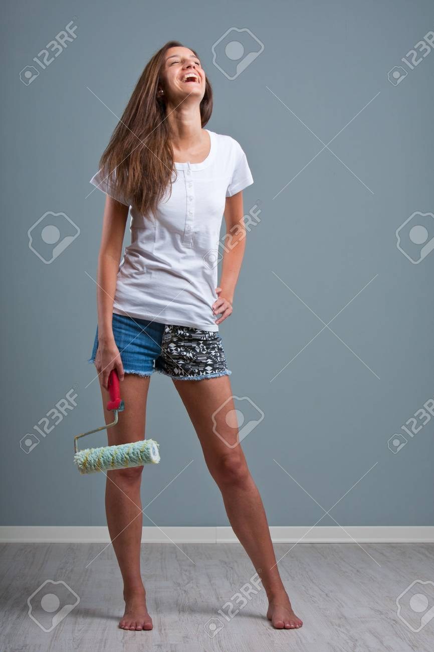 wonderful slim woman with paint roller laughing stock photo, picture