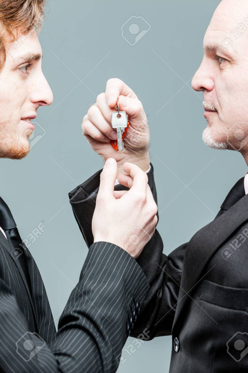 Concept of a generations business turnover with a solemn senior businessman handing over a key to a smiling younger man in a close up view of their hands and faces - 60898021
