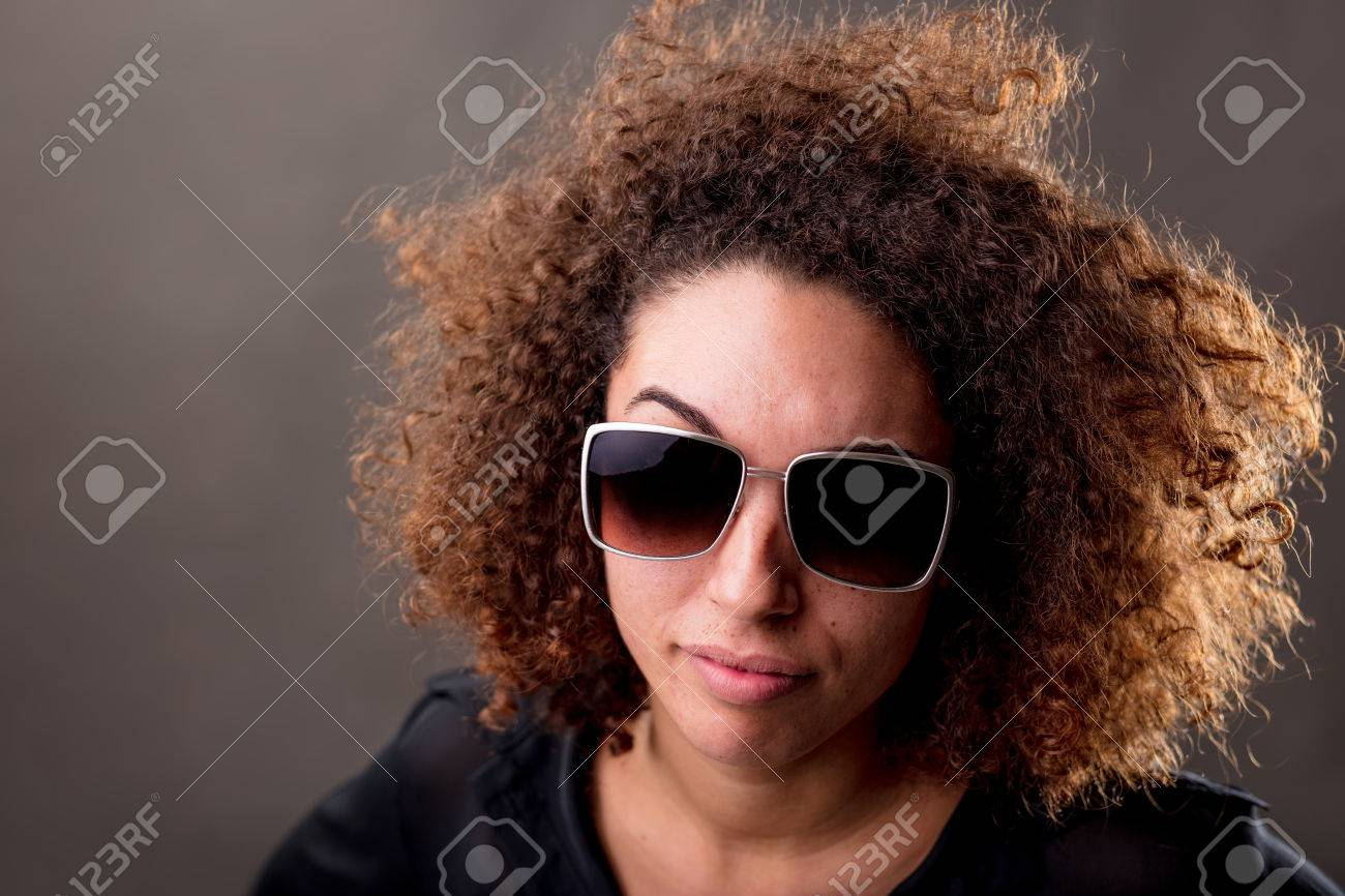 2cabc64102c impudent curly haired young woman with sunglasses watching you in a very  skeptical attitude Stock Photo