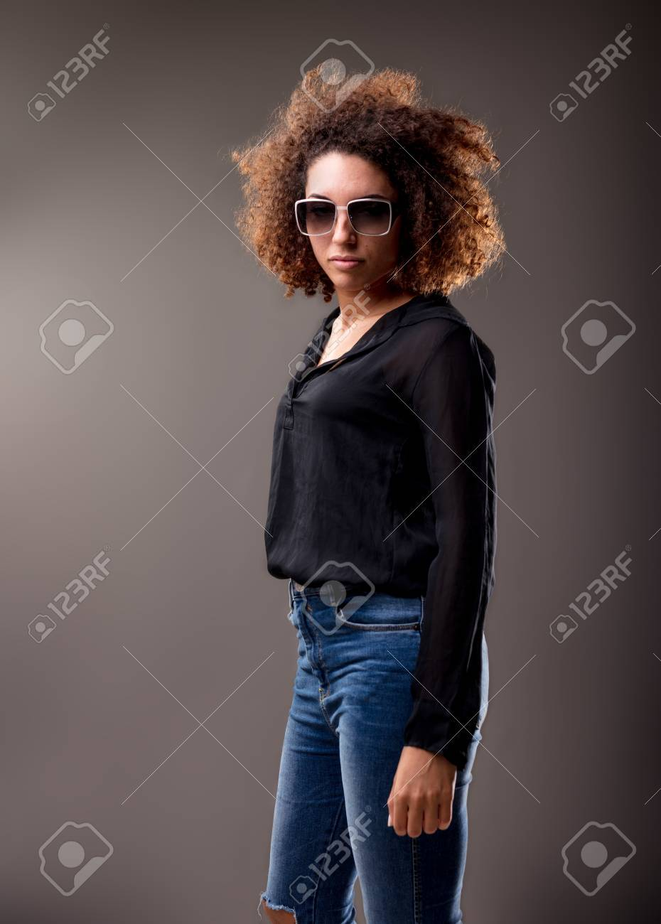 9a76367114c Stock Photo - woman with afro hair and sunglasses standing proud and watching  you