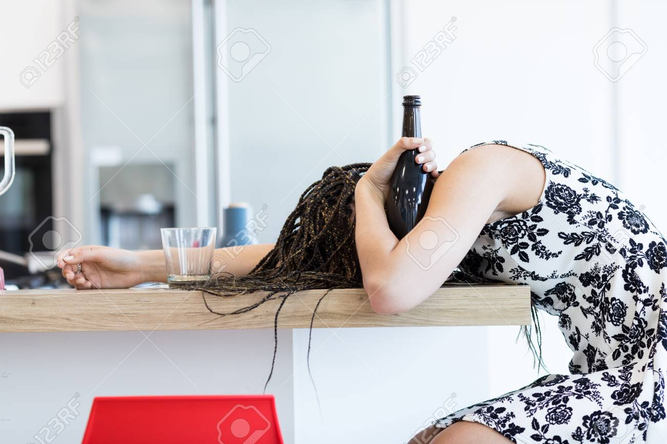 e807ad13763f Side view of drunk young woman with braids lying on table face down and  holding a