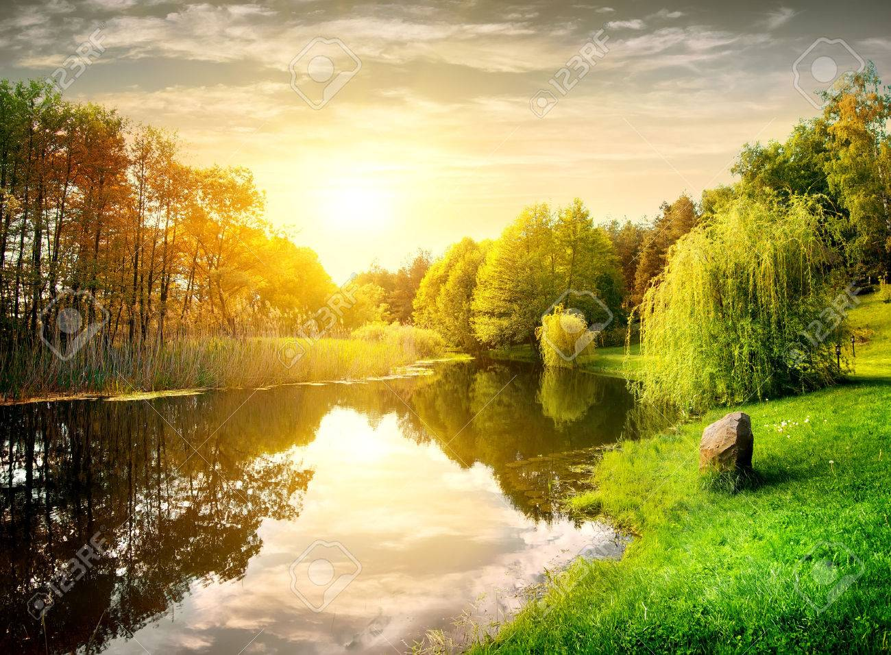 Sunset over calm river in the park Stock Photo - 43674596