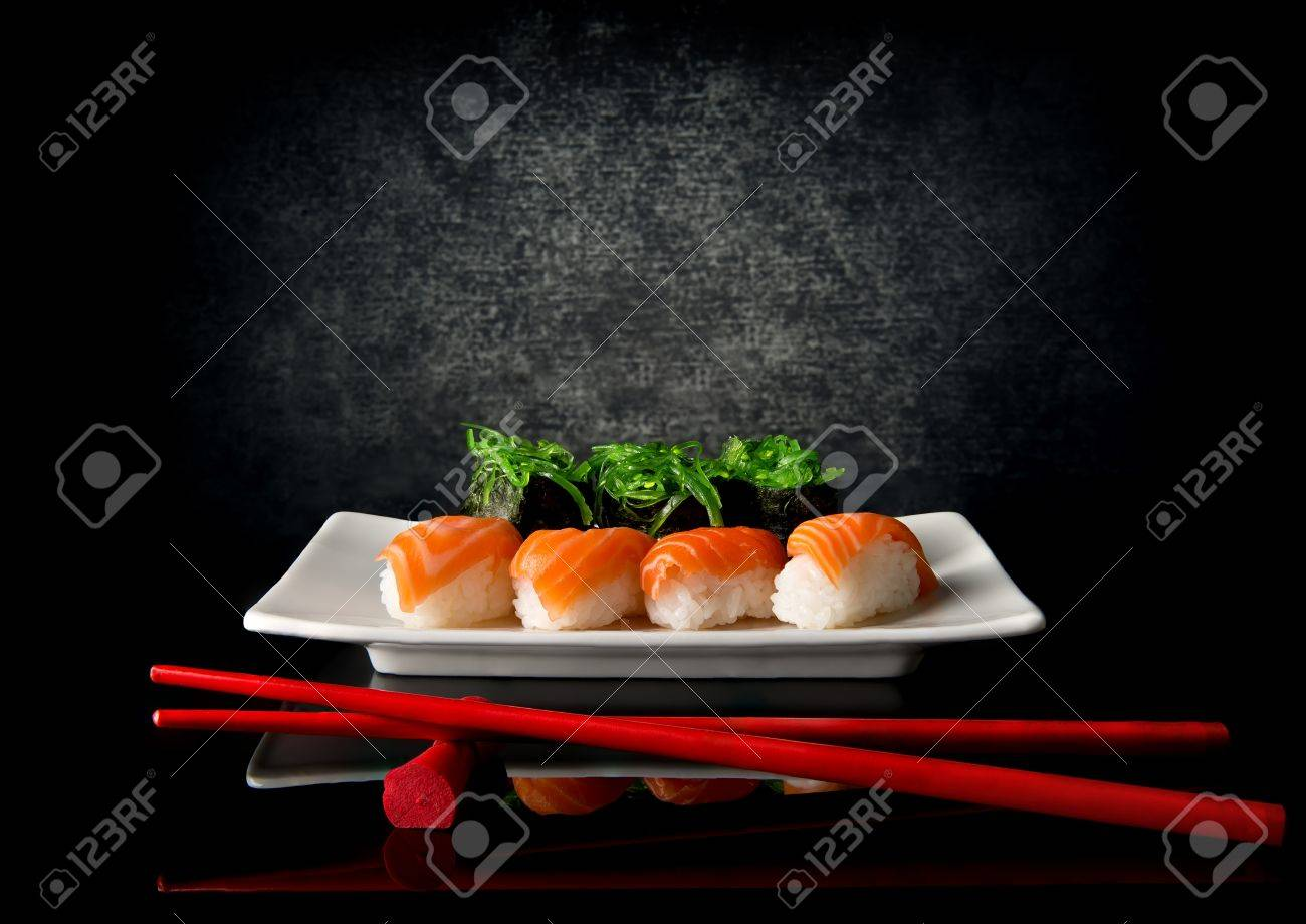 Sushi on plate with red chopsticks on black background - 50561058