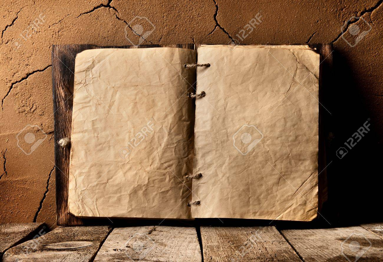 Opened old book on table near clay wall - 54300916