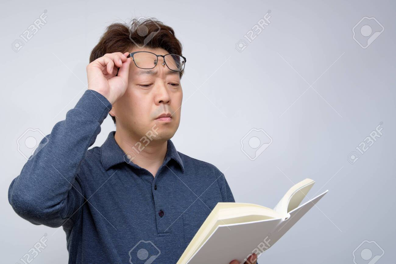 Asian male trying to read something in his book. poor sight, presbyopia, myopia. - 135564223