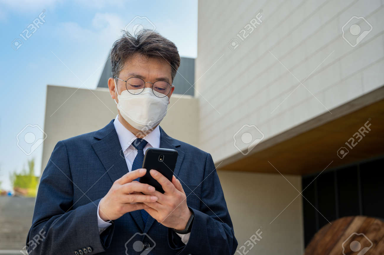 Middle-aged Asian businessman in the city wearing a mask and using a smartphone. - 167986731