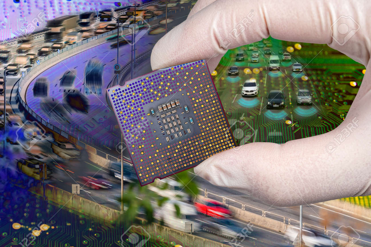 The computer circuit board and fast-moving cars. A hand holding a CPU chipset. - 169818840