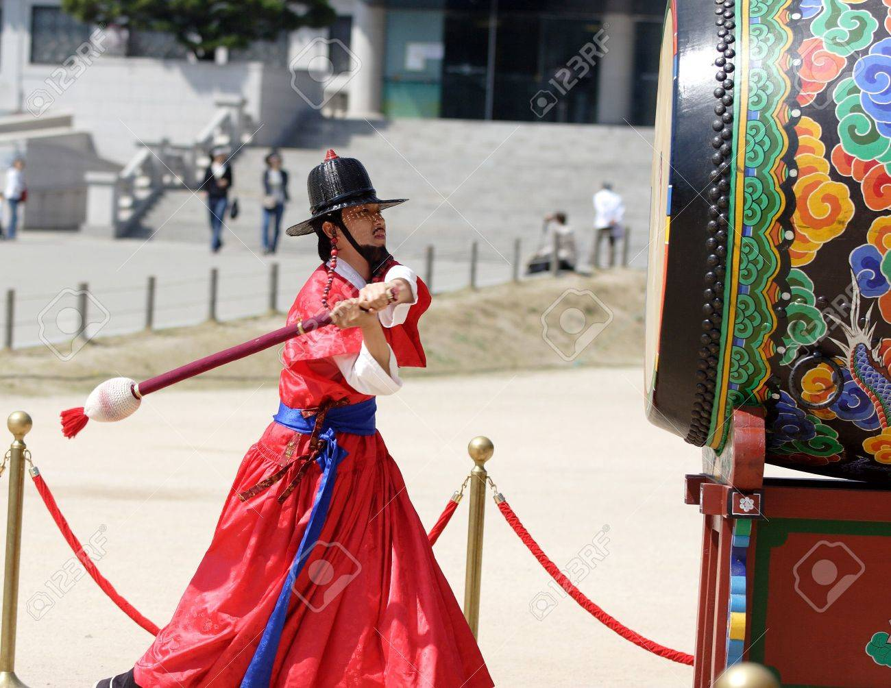 Korean man in traditional costume beats the drum to signal the changing of the guard at Kyoungbok Palace in Seoul, Korea. 04/16/2008 - 6886161