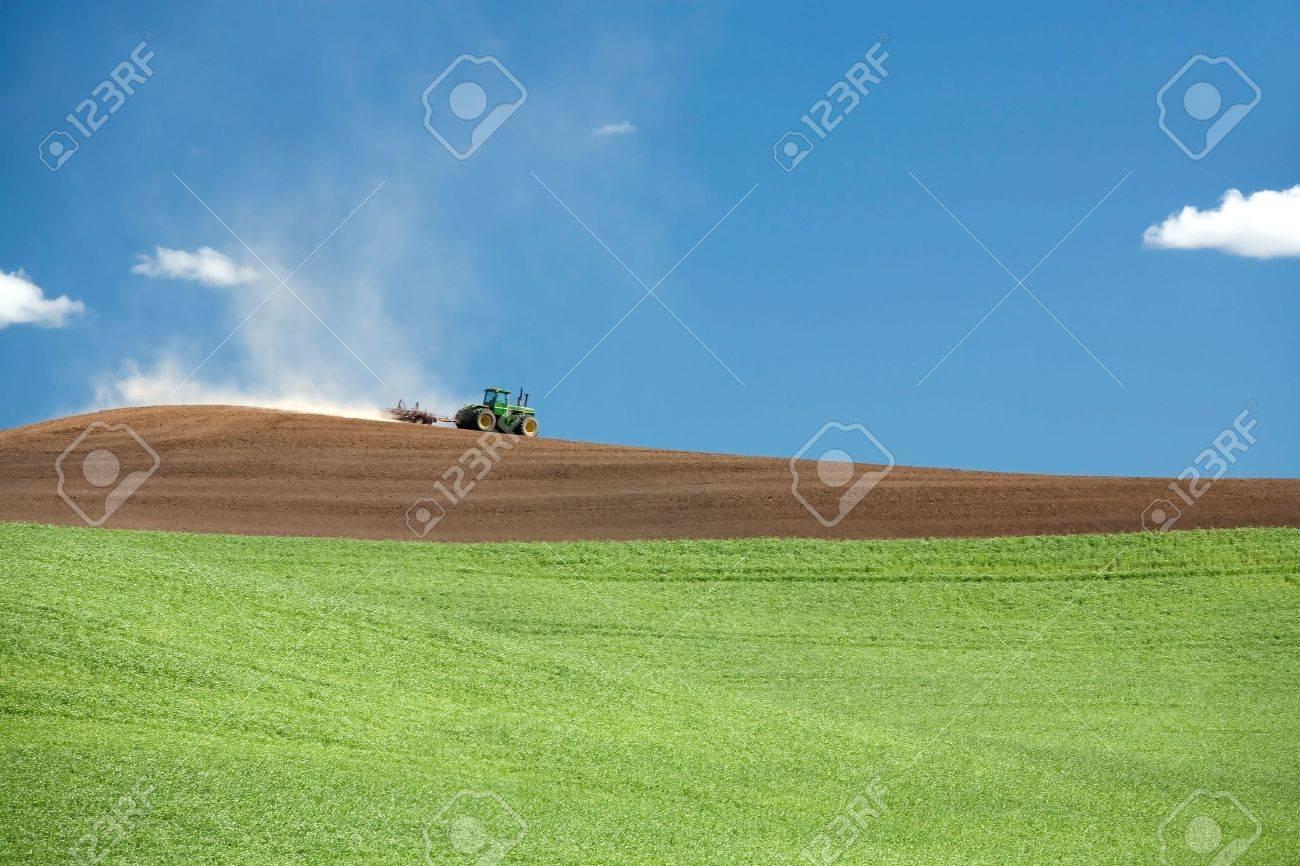 A tractor moves its way across a field in the palouse region near Steptoe, Washington. - 7420259