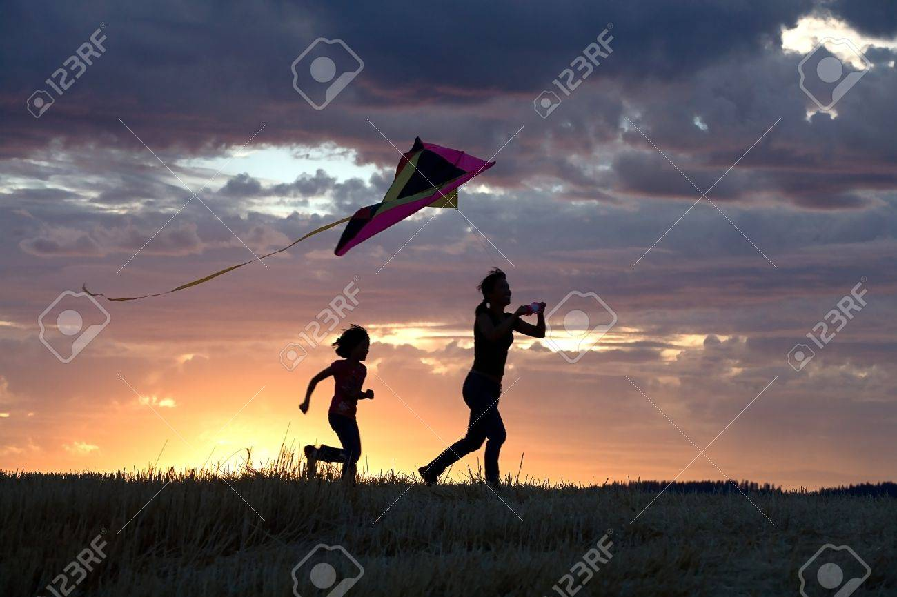 A mother runs to fly a kite with her daughter behind her. - 7748944