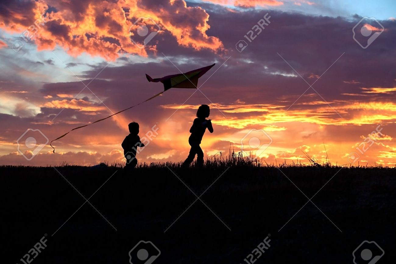 A girl flies a kite at sunset while her brother runs after. - 7748937
