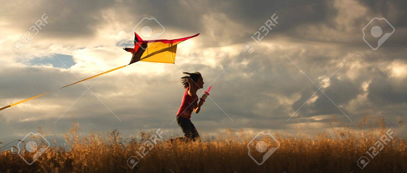 A panorama of a girl happily flying her kite. - 7748828