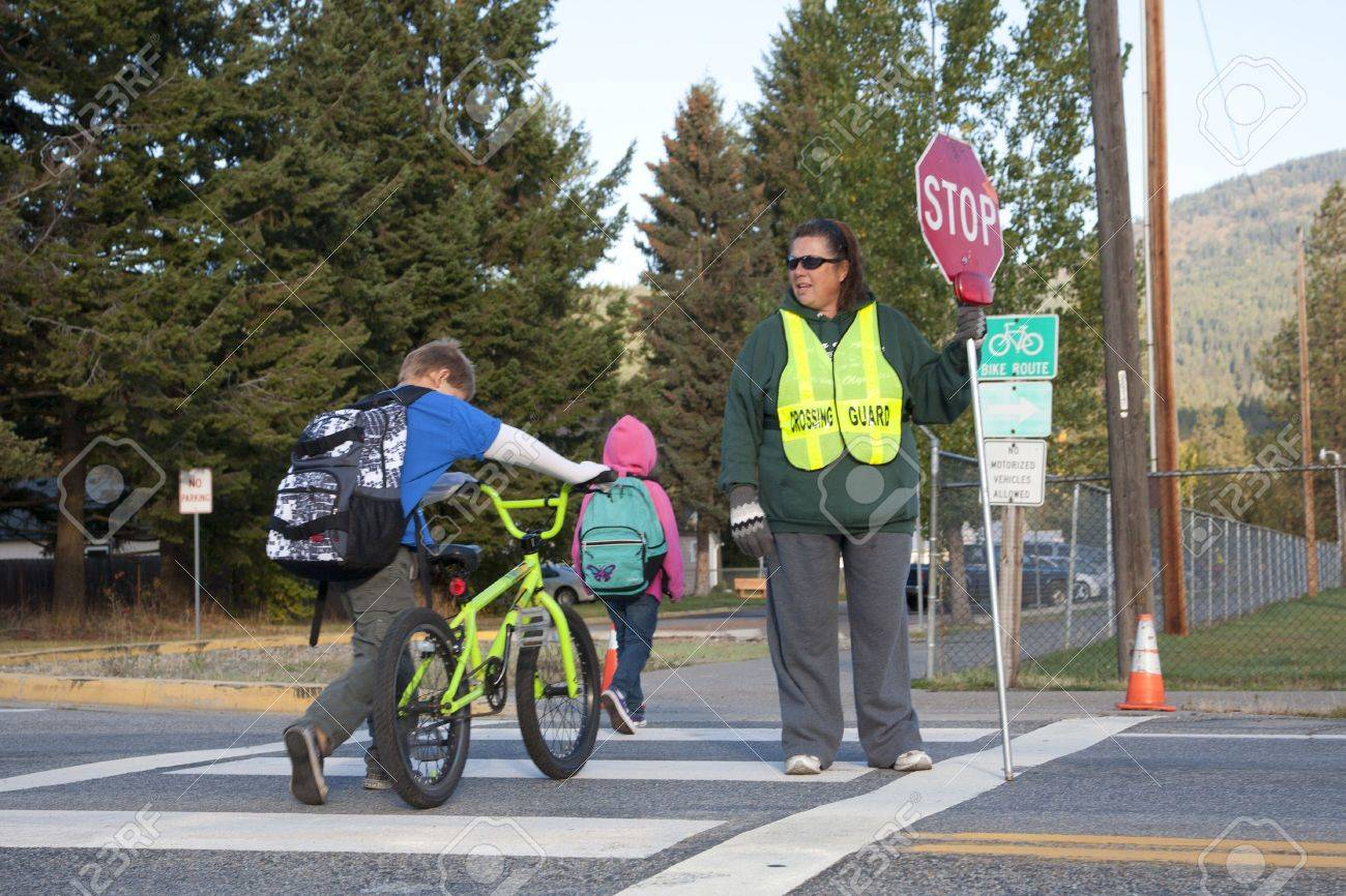 Rathdrum, Idaho. October 4, 2010. Unidentified crossing guard stops traffic for kids crossing the street in Rathdrum Idaho on October 4, 2010. - 7959693