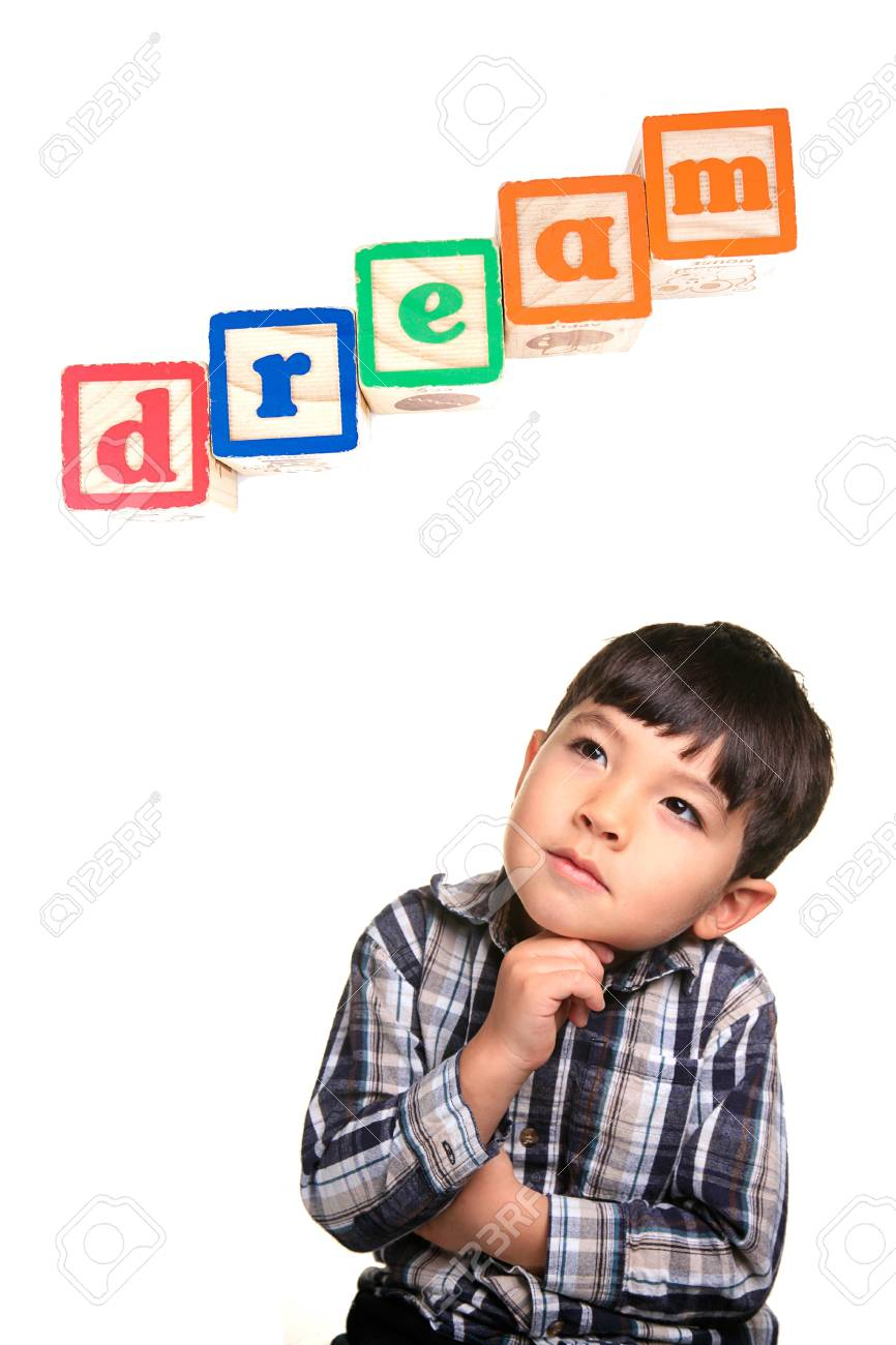 A young boy in a day dreaming pose under the word blocks. Stock Photo - 8419821