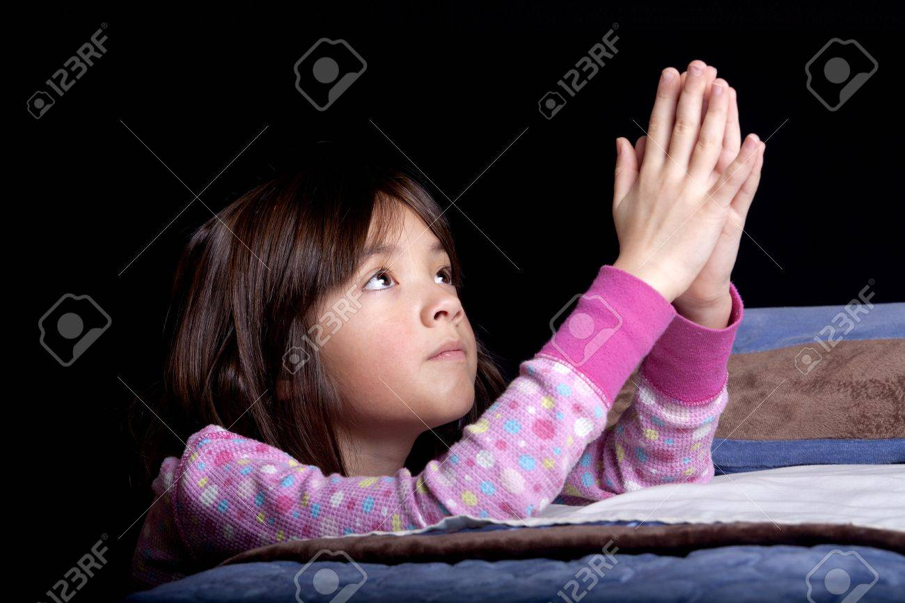 A young girl says her prayers just before bed time. - 8681711