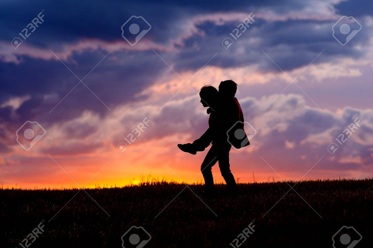 A young girl carries her brother on her back at sunset. - 10741242