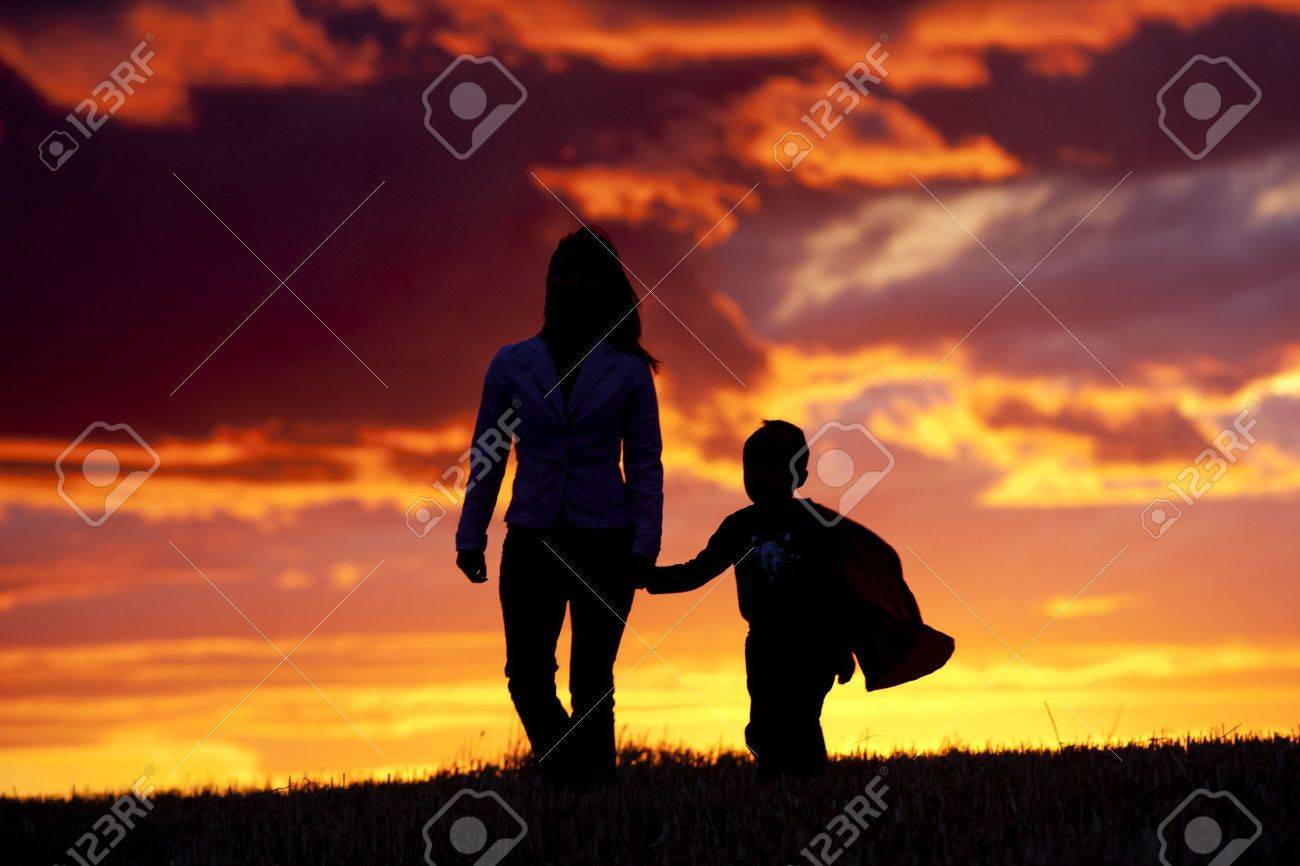 A tender moment of a mom and her son walking along at sunset. - 10741247