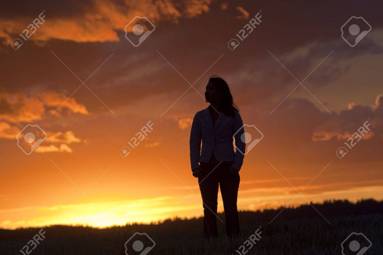 A woman silhouetted by the back light of the sunset stands alone in a field. - 10749561