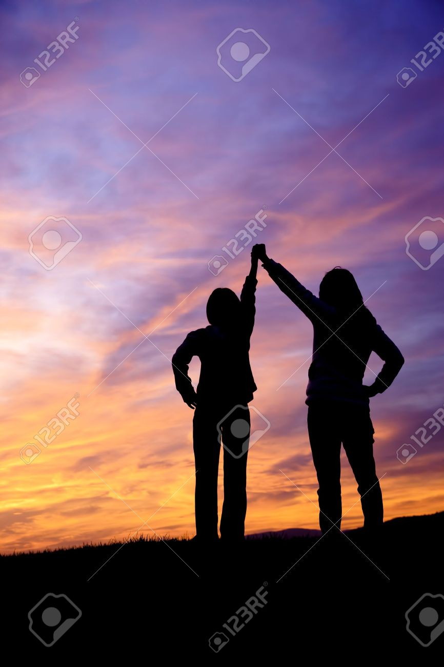 A mother and daughter holding raised hands watch the sunset - 15584884