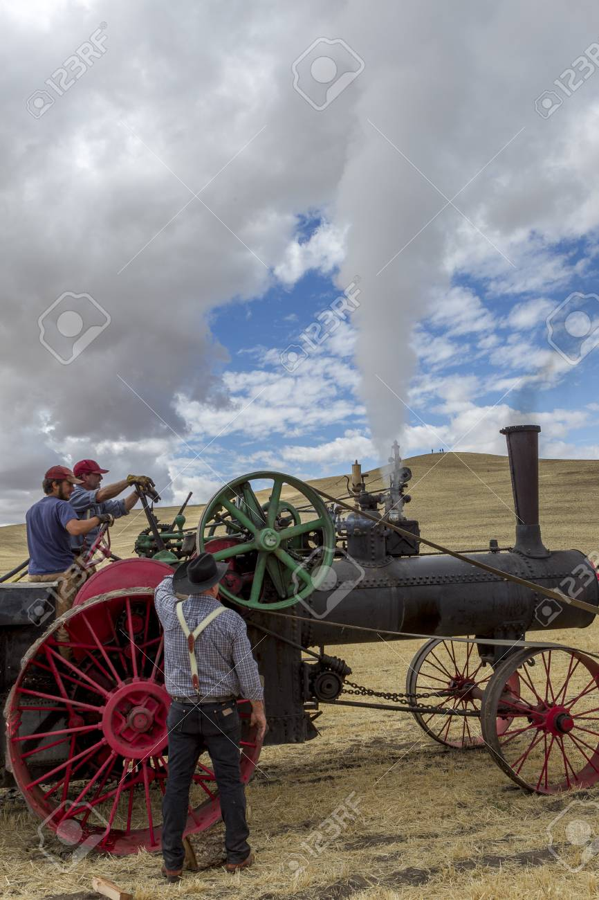Men Working On A Steam Engine At The Old Fashioned Threshing.. Stock ...