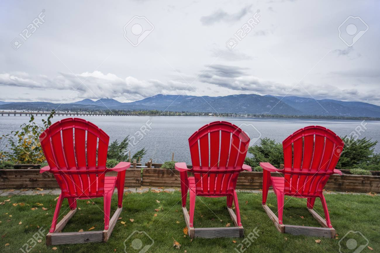 Stock Photo   Three Red Lawn Chairs Sit In The Yard Overlooking The Lake By  Sandpoint, Idaho.